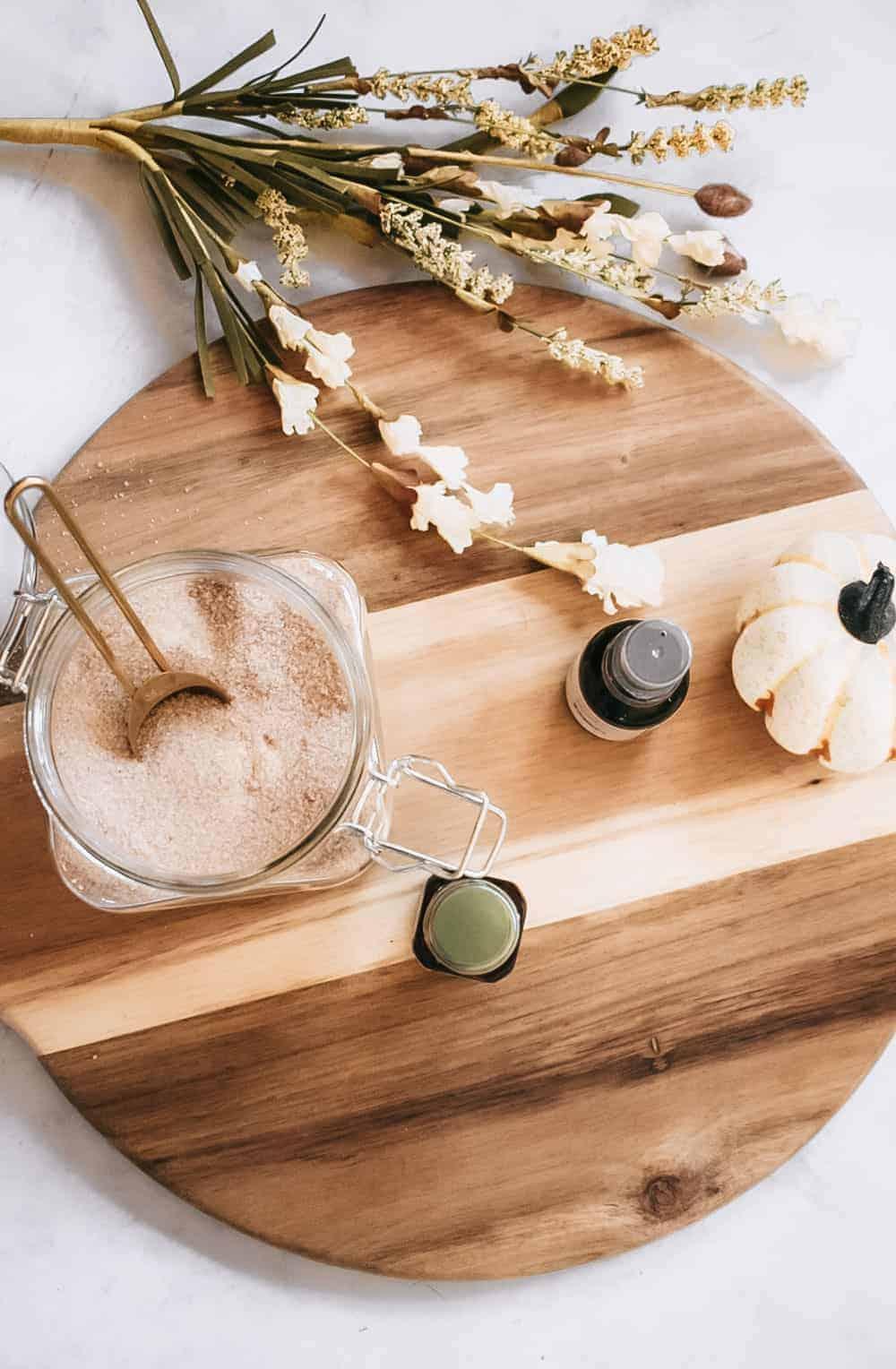 ingredients for diy pumpkin spice body scrub on round cutting board next to fall foliage and fake pumpkin