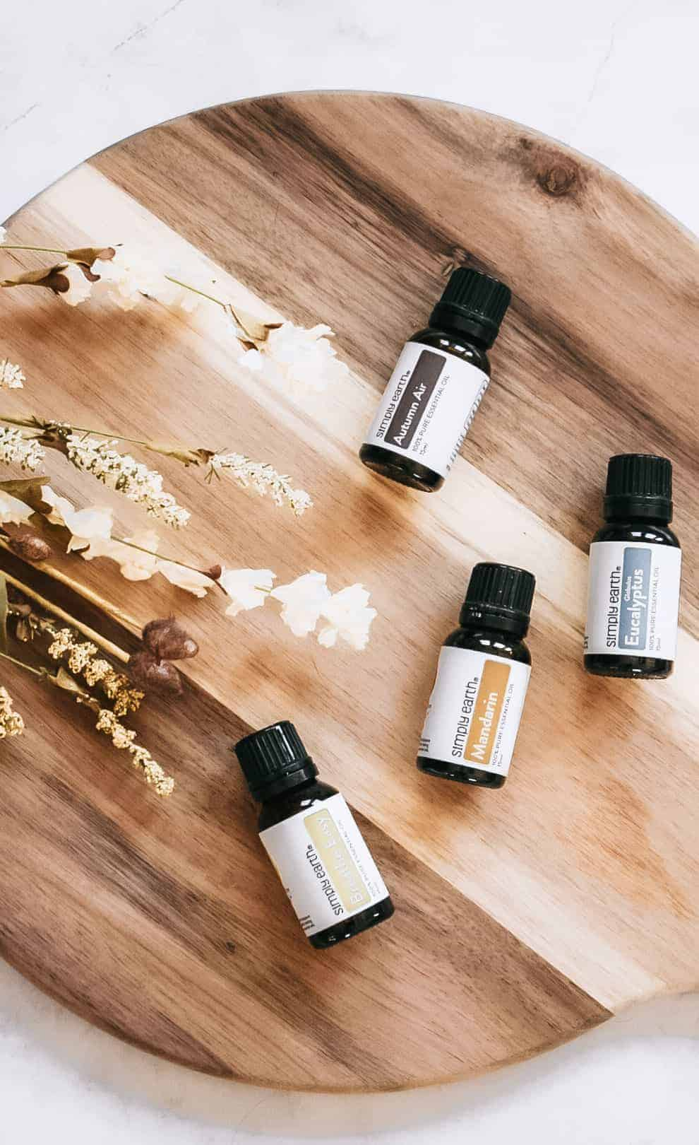 Simply Earth essential oils lying on wooden cutting board next to fall foliage