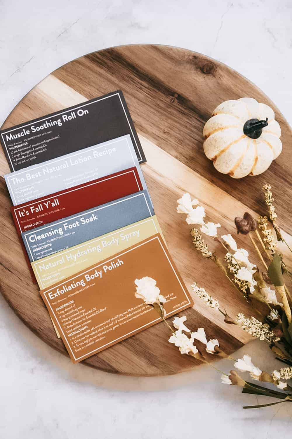 Simply Earth recipe cards laid out on a wooden cutting board next to small pumpkin and fall foliage