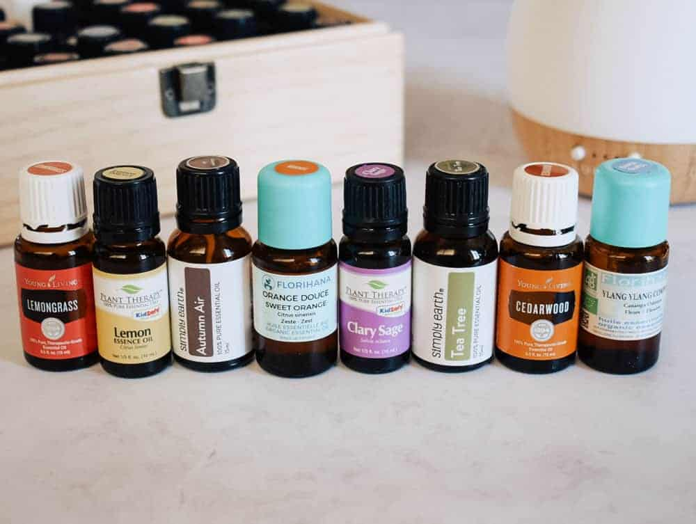 Young Living, Florihana, Plant Therapy, and Simply Earth essential oils all lined up in front of essential oil diffuser and essential oil storage box