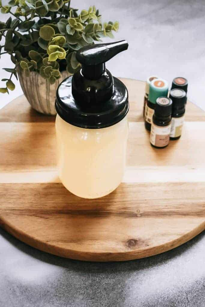 Homemade foaming hand soap sitting on round cutting board next to essential oils.