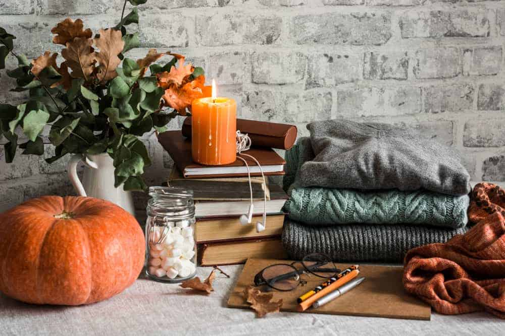 fall decor, candles, sweaters and foliage sitting in front of brick wall