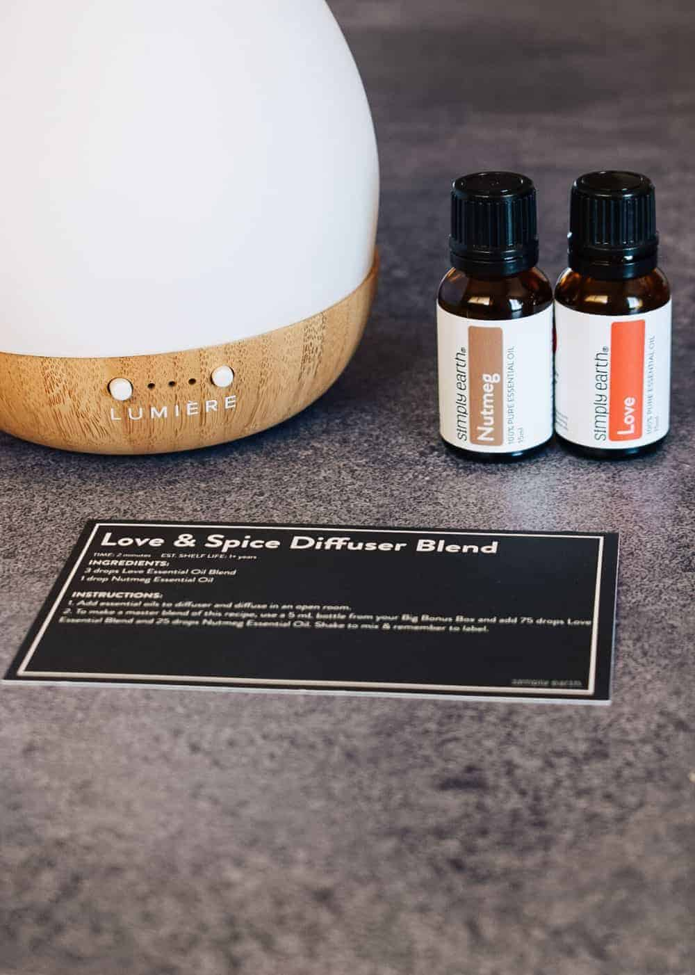 Love essential oil blend and nutmeg essential oil next to lumiere essential oil diffuser
