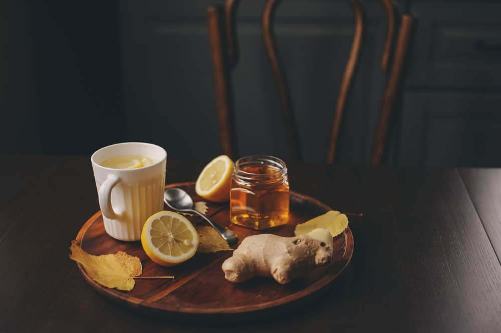 flu bomb tea drink sitting on kitchen table next to honey, lemon, and ginger