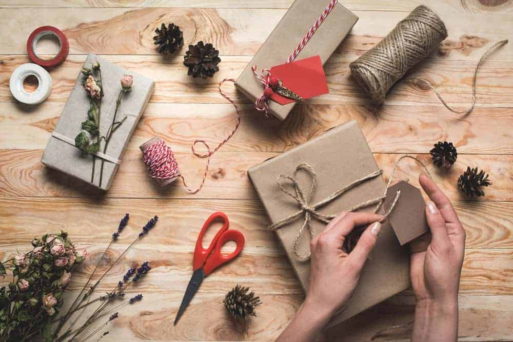 person wrapping gifts with kraft paper