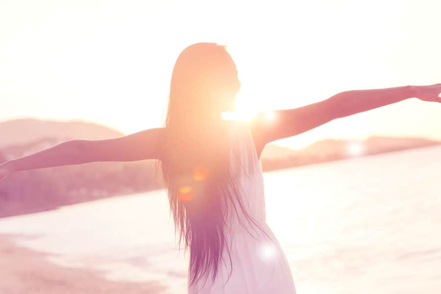 photo of a woman standing in the sun with her arms stretched out