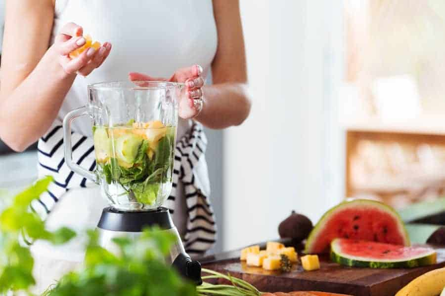 woman living a healthy lifestyle by making a smoothie