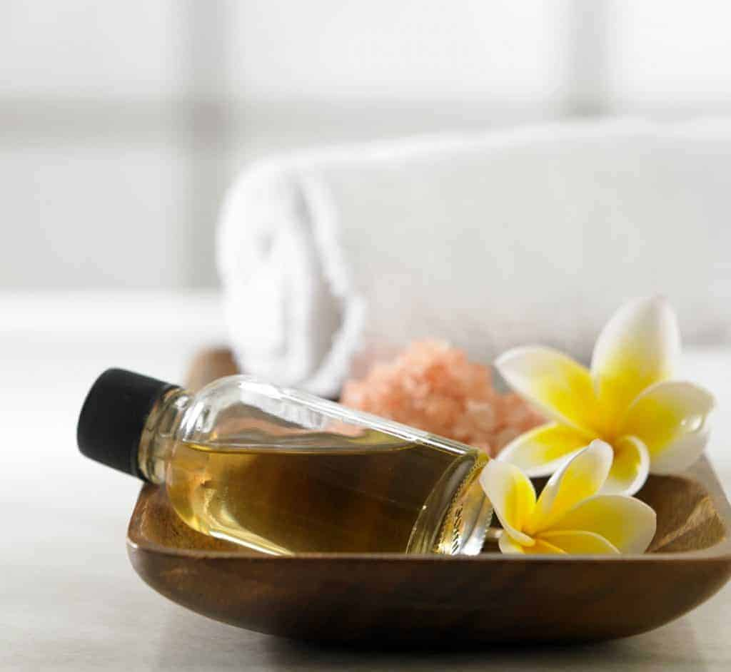 DIY massage oil next to flowers and white towels.
