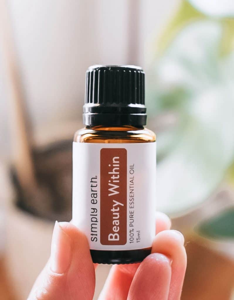 Person holding Simply Earth Beauty Within essential oil blend.