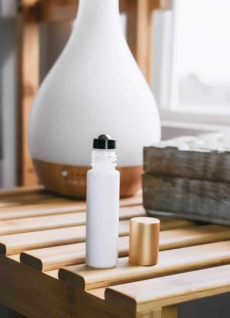Sore muscle relief essential oil roller next to essential oil diffuser.