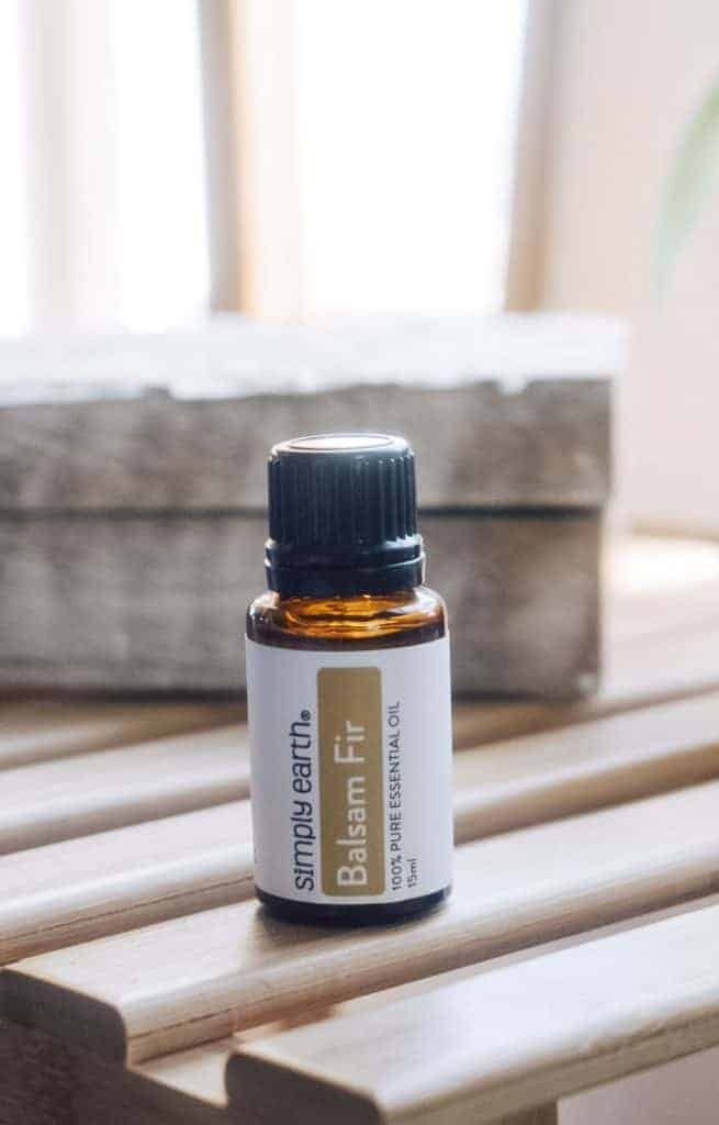 Simply Earth Balsam Fir essential oil on wooden table.