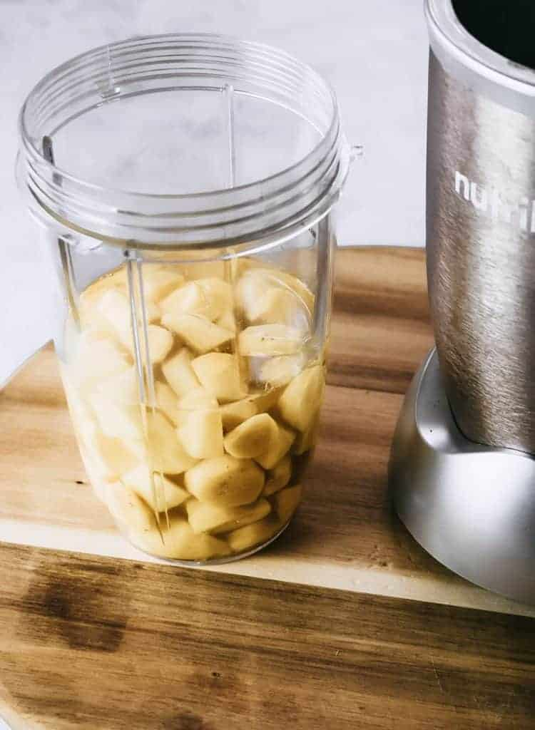 Cut up ginger in cup next to blender.