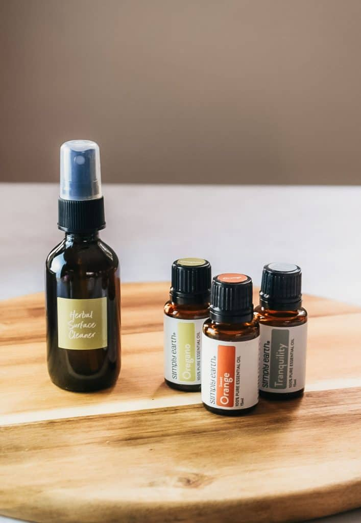 Homemade herbal surface cleaner next to essential oils on cutting board.