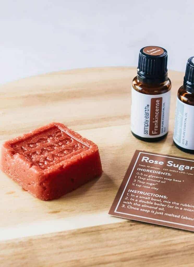 Homemade rose sugar scrub soap next to essential oils.