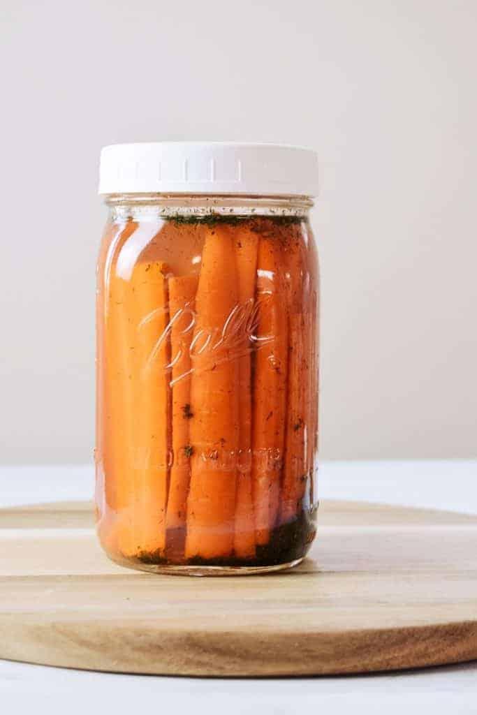 Fermented carrots on cutting board in jar.