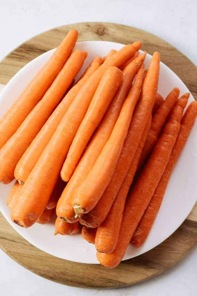 Washed carrots on white plate.