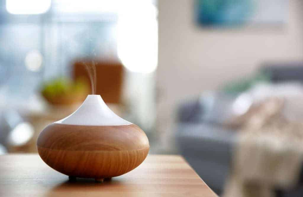 Essential oil diffuser sitting on end table beside bed.